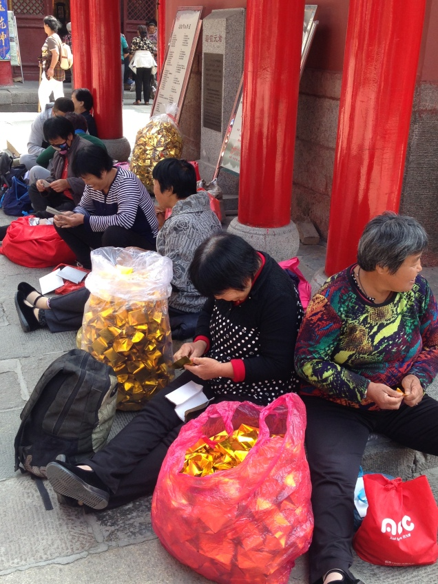 women making fake gold ingots to be used as offerings on Taishan